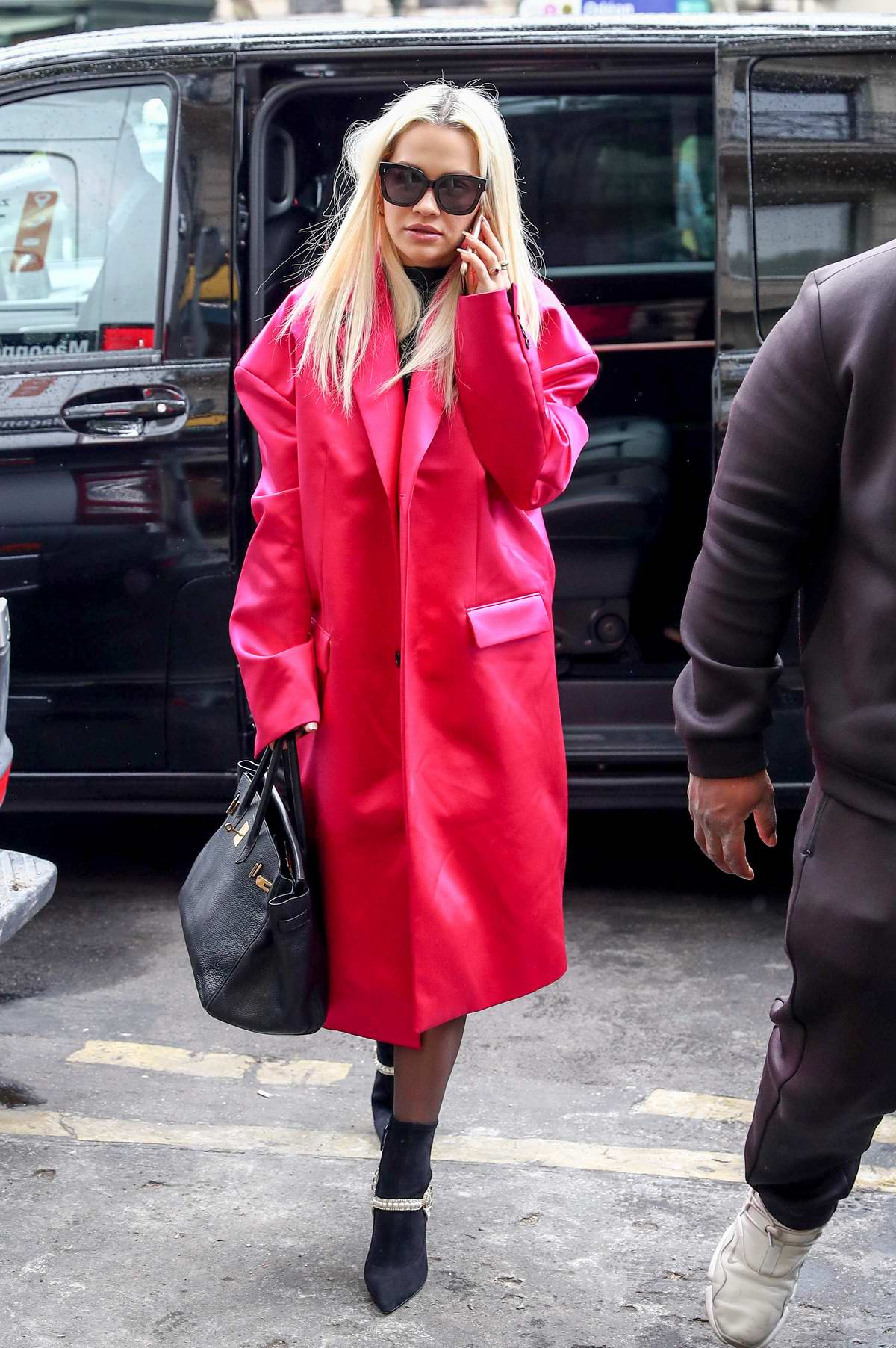 Rita Ora stands out in a fuchsia coat as she leaves Hotel Costes in Paris, France