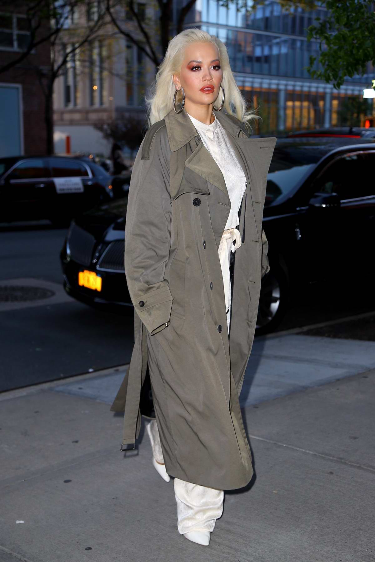 Rita Ora wears an olive green long coat with an all white outfit as she arrives at the Greenwich Hotel in New York City