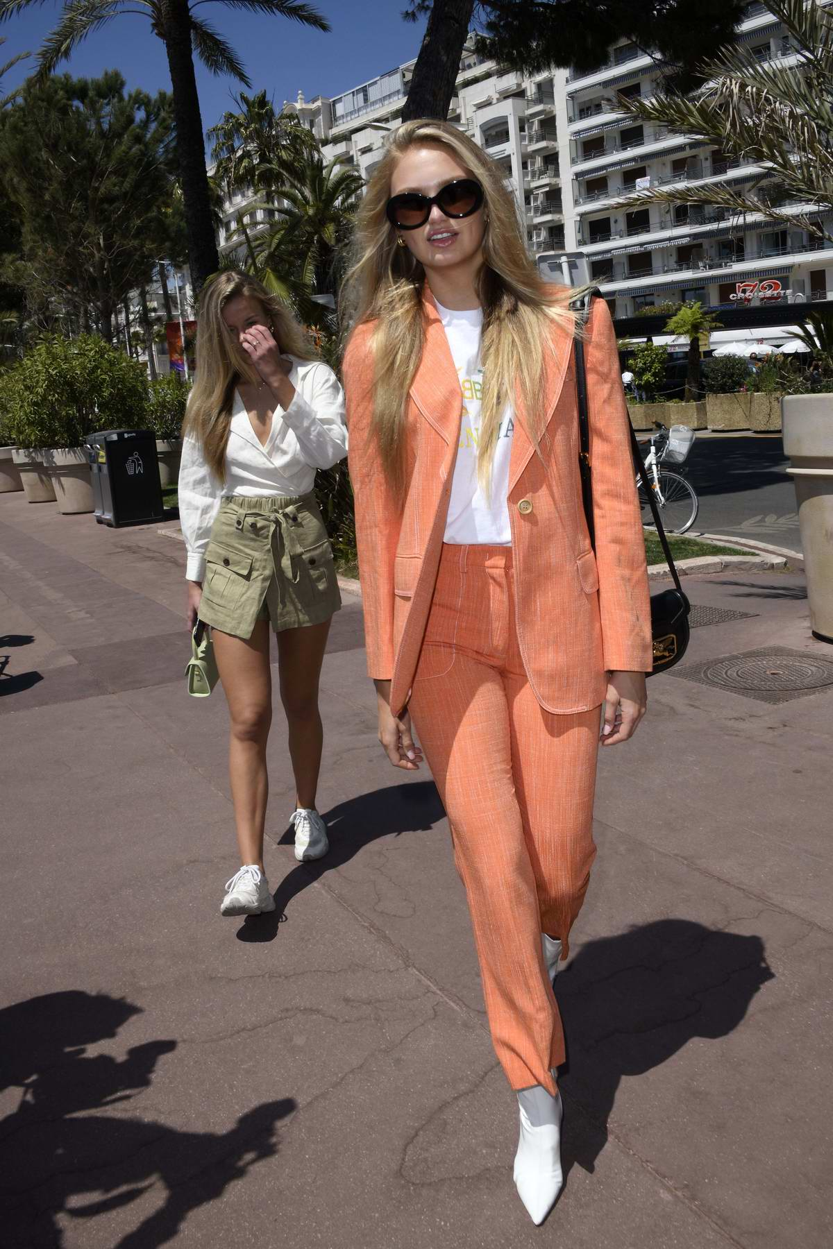 Romee Strijd steps out wearing an orange suit on the Croisette during the 72nd Cannes Film Festival in Cannes, France