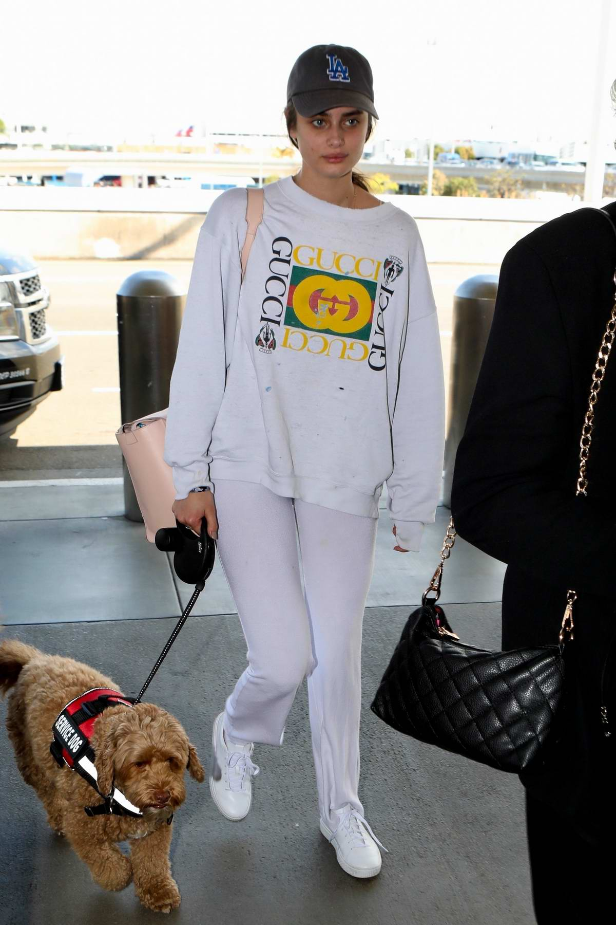Taylor Hill and her service dog arrives to board a flight at LAX Airport in Los Angeles