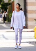 Alessandra Ambrosio radiates in a white sweatshirt with matching leggings and sneakers while out in Brentwood, Los Angeles