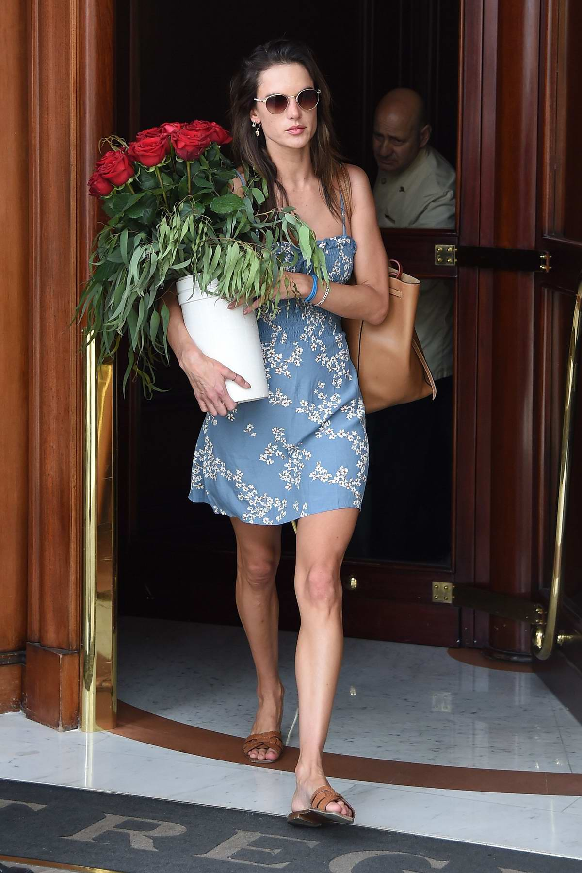 Alessandra Ambrosio wears a floral print blue dress and carries a bouquet of red roses as she leaves her hotel in Florence, Italy