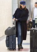 Anne Hathaway pushes her own luggage as she arrives for a flight at JFK Airport in New York City