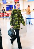 Bella Hadid looks trendy in camouflage sweater and black pants as she touches down JFK airport in New York City