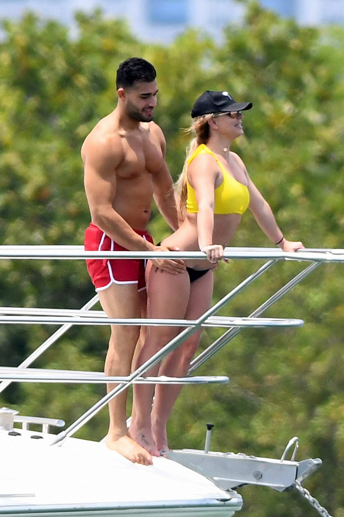 Britney Spears wears a yellow and black bikini while enjoying a day on a Yacht with boyfriend Sam Asghari in Miami, Florida