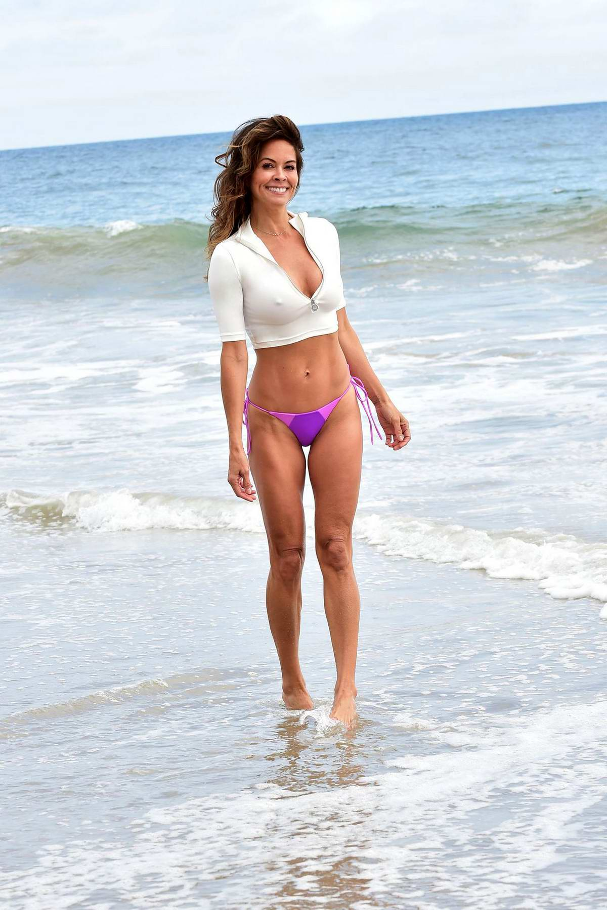 Brooke Burke enjoys the beach in a crop top and bikini bottoms in Malibu, California