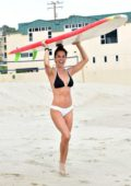 Brooke Burke sports a black and white bikini as she hits the beach with a surfboard in Malibu, California
