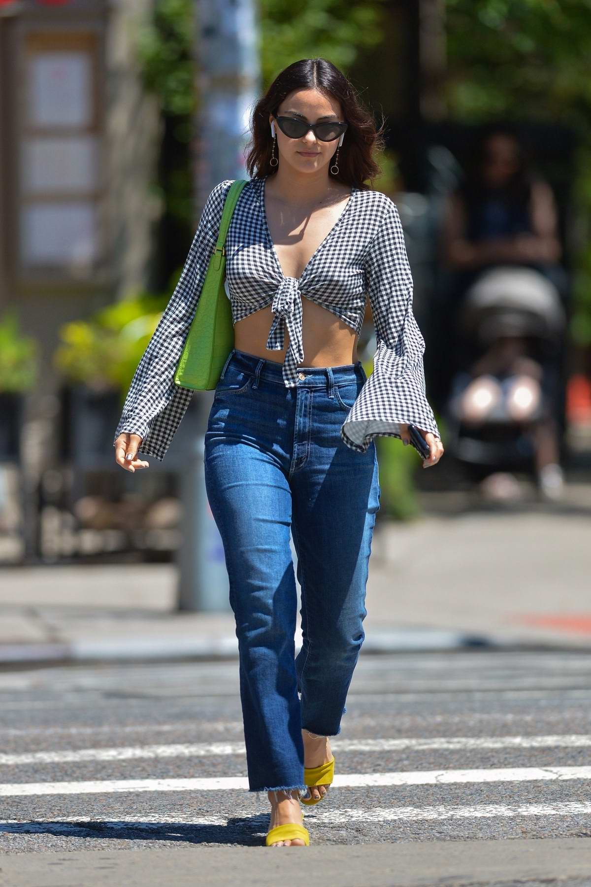 Camila Mendes wears a checkered crop top and jeans while out for a walk with Charles Melton in New York City