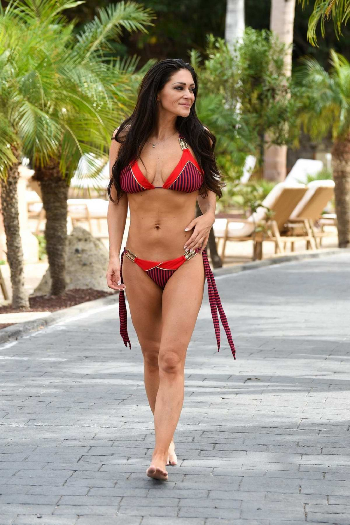 Casey Batchelor wears red bikini while catching some rays during her holiday in Italy