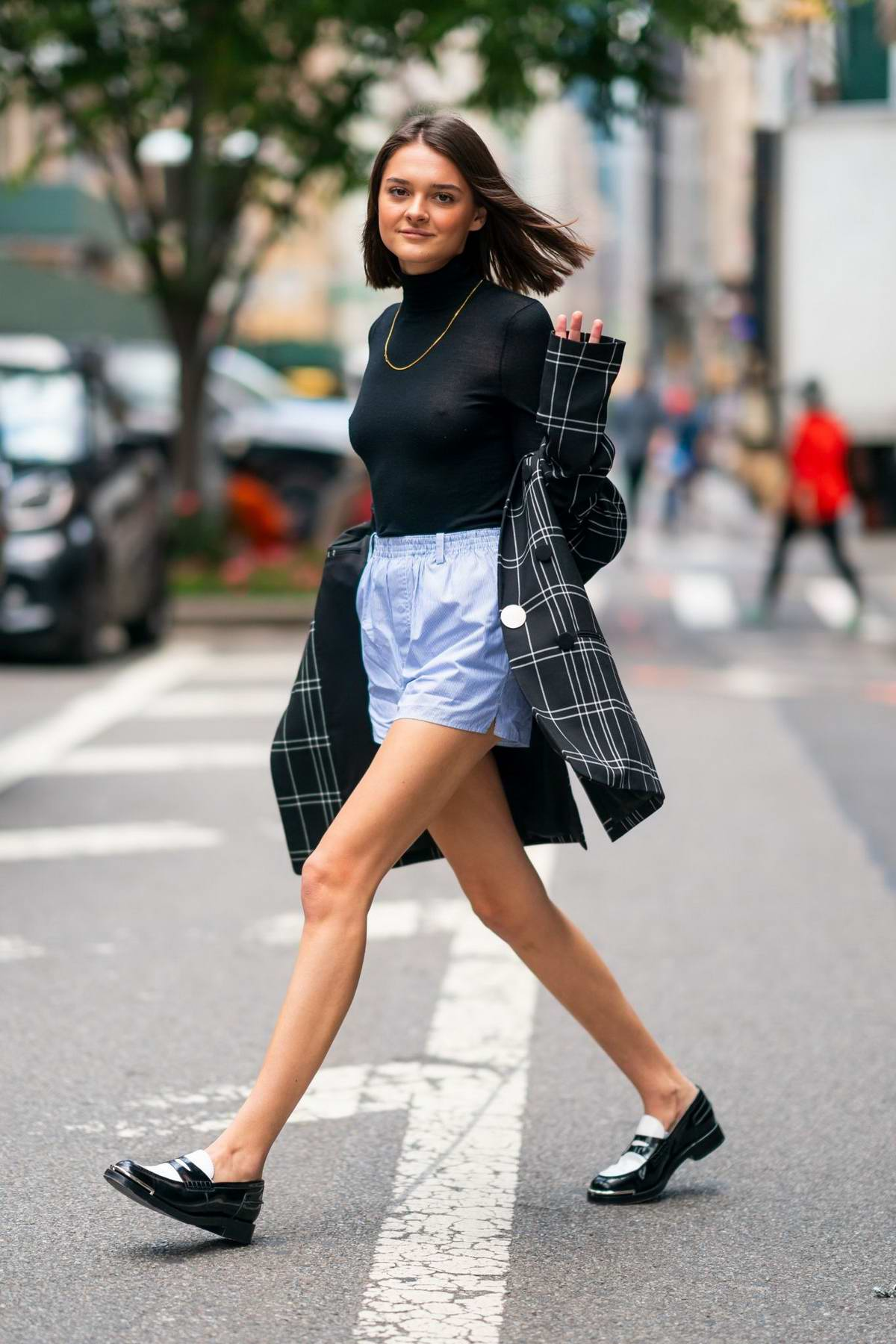 Charlotte Lawrence looks stylish in a plaid blazer, black top and blue shorts as she steps out in New York City