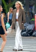Elsa Hosk keeps it stylish with a brown blazer with a white crop top and off-white pants while out for a stroll in New York City