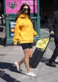 Emily Ratajkowski rocked a bright orange hoodie and black legging shorts as she heads out with her luggage in New York City