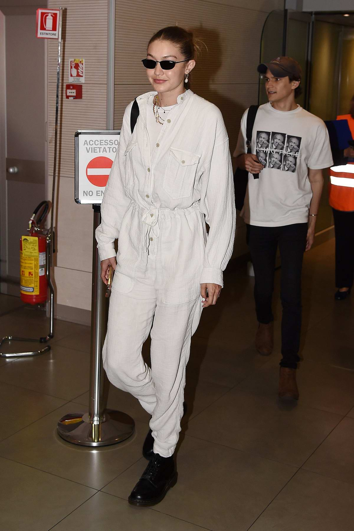 Gigi Hadid sports white jumpsuit and Prada backpack as she arrives at Florence airport, Italy