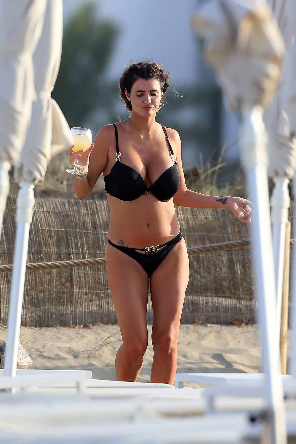 Helen Wood dons a black bikini while having a good time at the beach with a friend in Ibiza, Spain