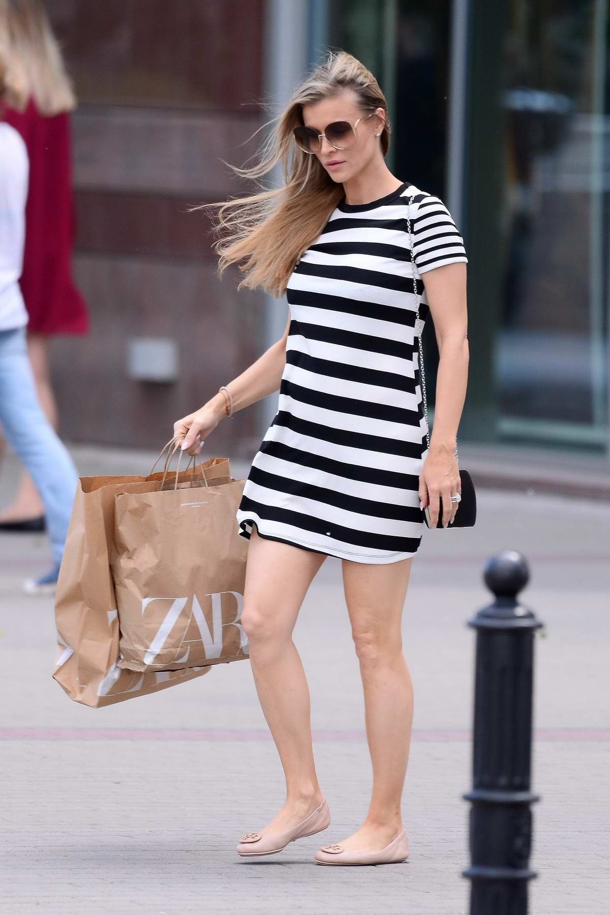 Joanna Krupa shows off her baby bump as she steps out in a monochrome striped dress in Warsaw, Poland