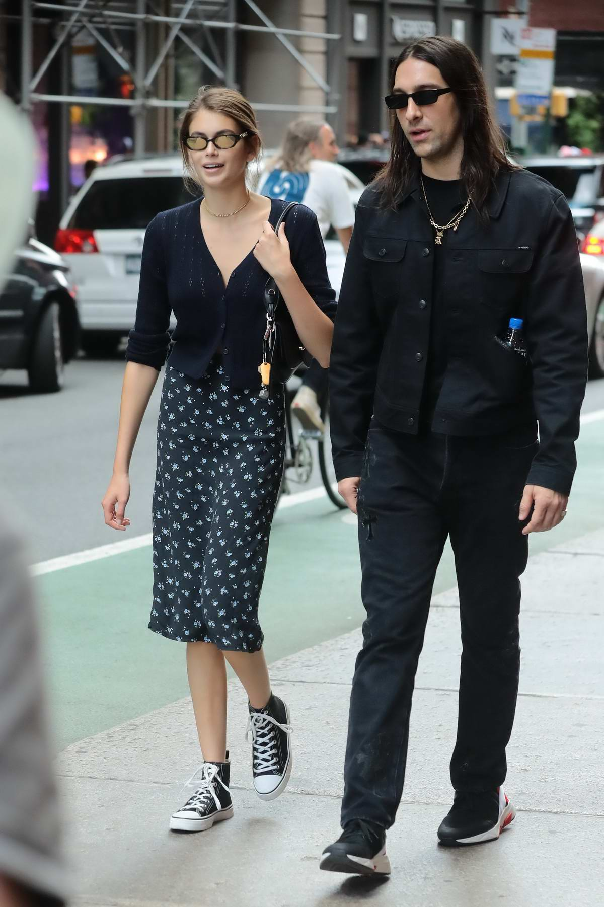 Kaia Gerber wears Chanel sunglasses with a black cardigan and patterned skirt while out for a stroll in New York City