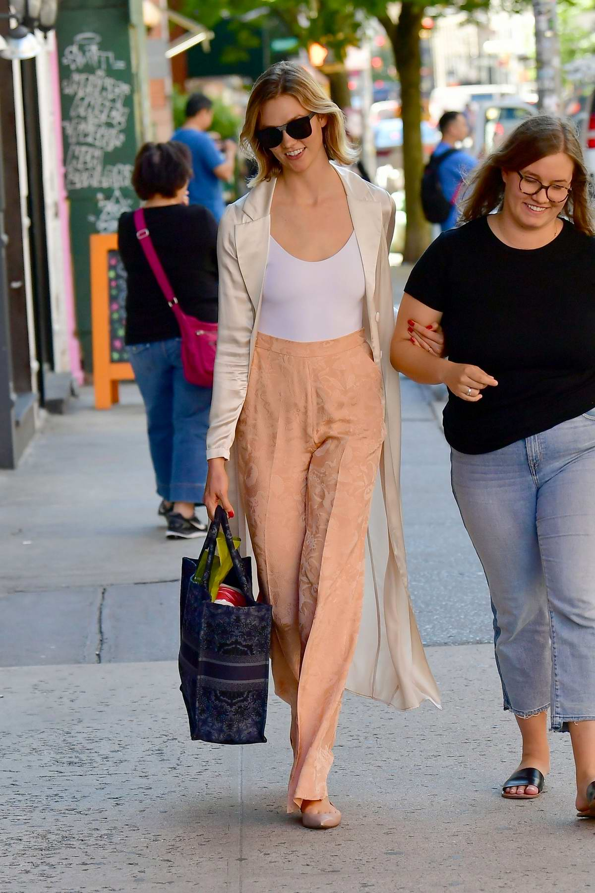 Karlie Kloss steps out with a smile and peach colored satin pants during an outing in New York City