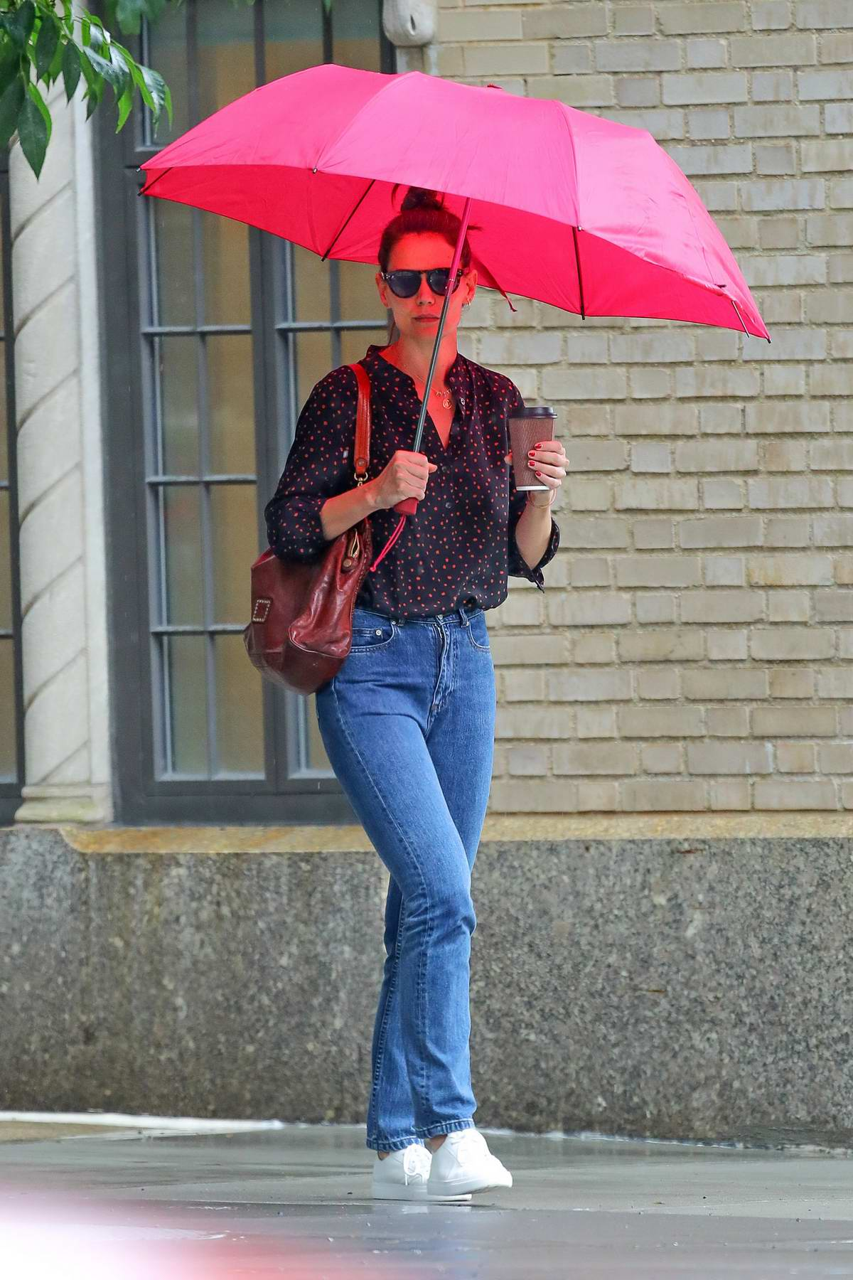 Katie Holmes sips on her coffee as she steps out on a rainy day with a bright pink umbrella in New York City