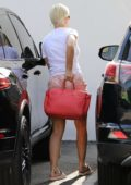 Katy Perry wears a white tee and pink velour shorts as she arrives at her Office in Los Angeles