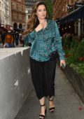 Kelly Brook seen wearing a blue silk animal print top and black pants as she steps out in London, UK