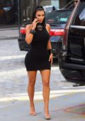Kim Kardashian dons a skintight black dress as she heads out with Jonathan Cheban in New York City