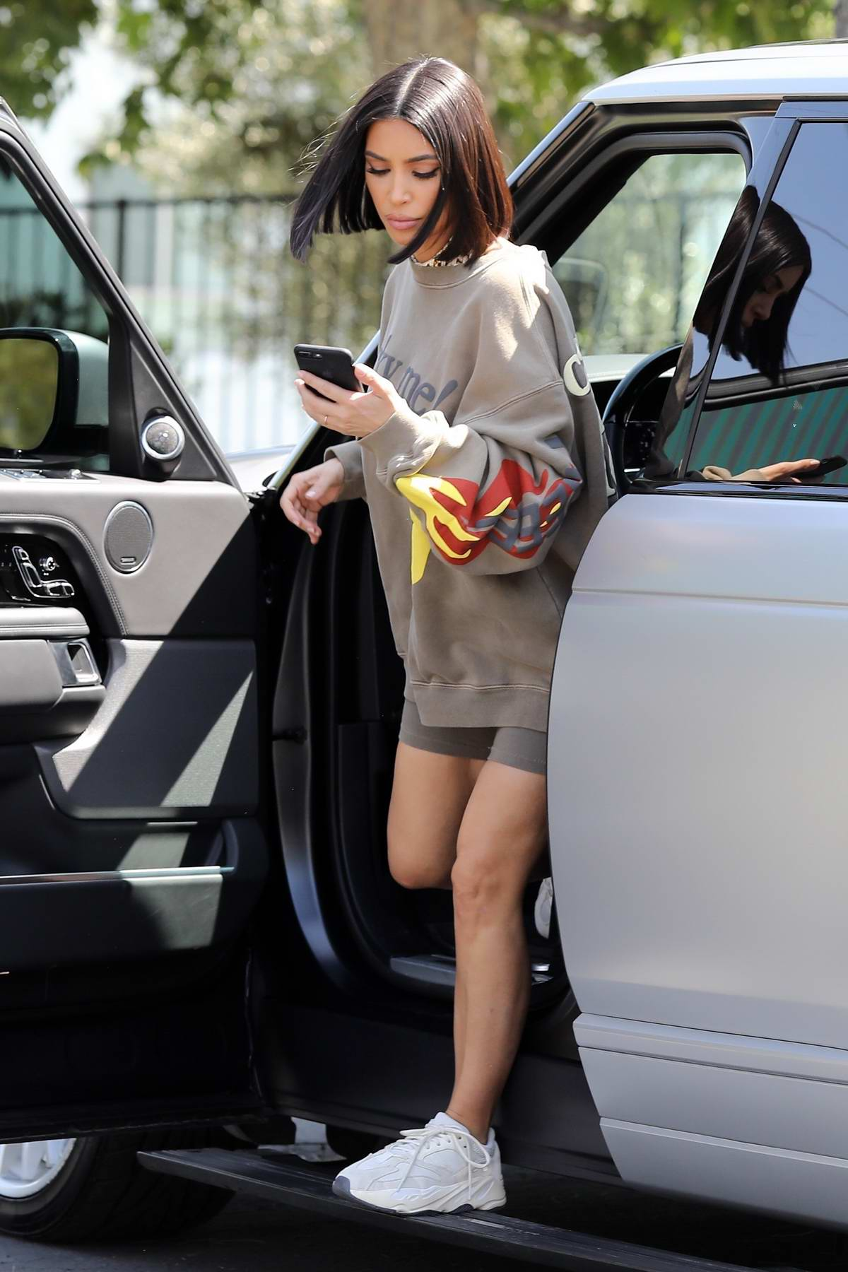 Kim Kardashian wears an oversized sweatshirt and shorts as she heads to a meeting at Kylie's office in Calabasas, California