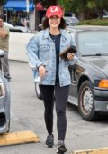 Lucy Hale wears a red 'LA' hat with denim jacket and black leggings during a coffee run to Alfred's in Studio City, Los Angeles