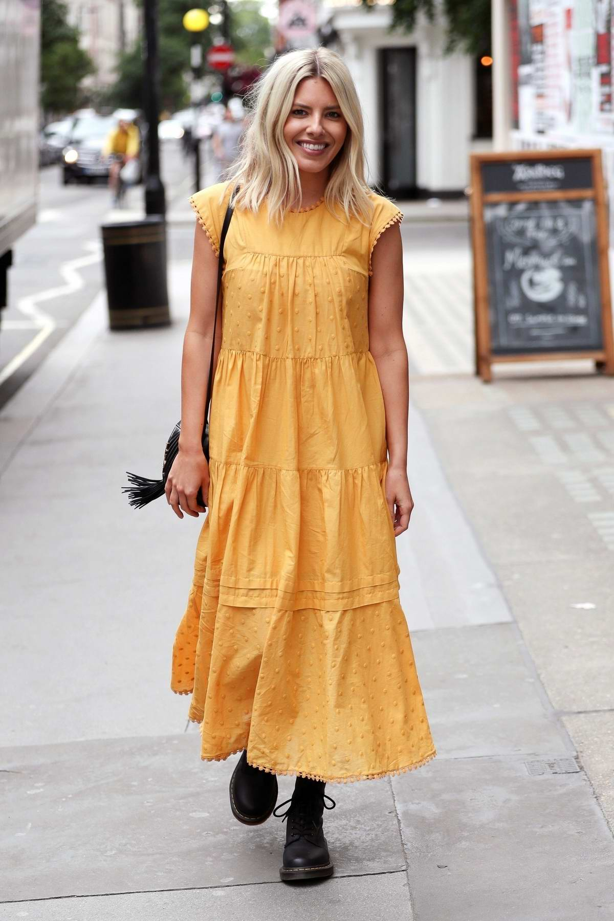 Mollie King seen wearing a yellow summer dress as she exits Juice bar in Soho, London, UK