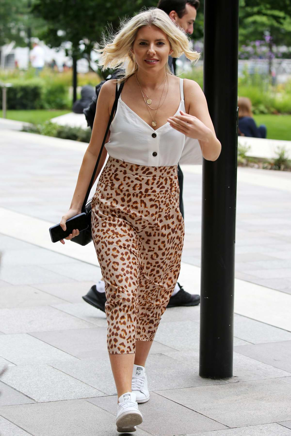 Mollie King wears a white camisole with leopard print skirt and sneakers as she arrives at ITV Studios in London, UK