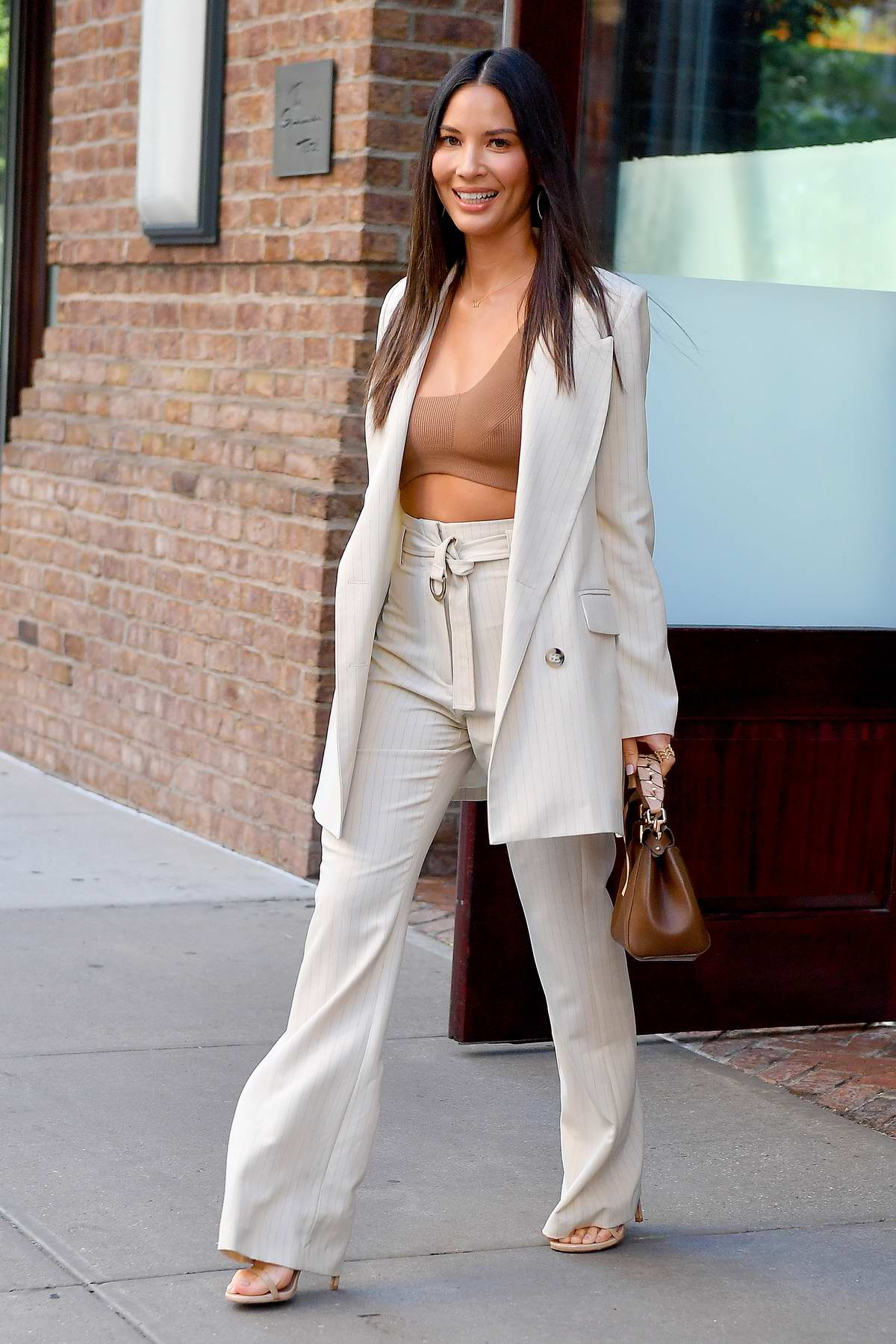 Olivia Munn steps out in a brown crop top and cream suit in New York City