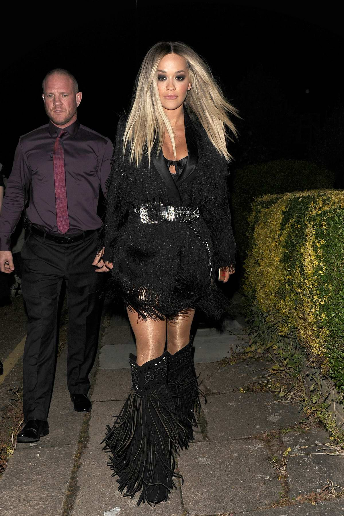 Rita Ora puts on a stylish display in tasseled black cowboy boots with a black dress while out in London, UK