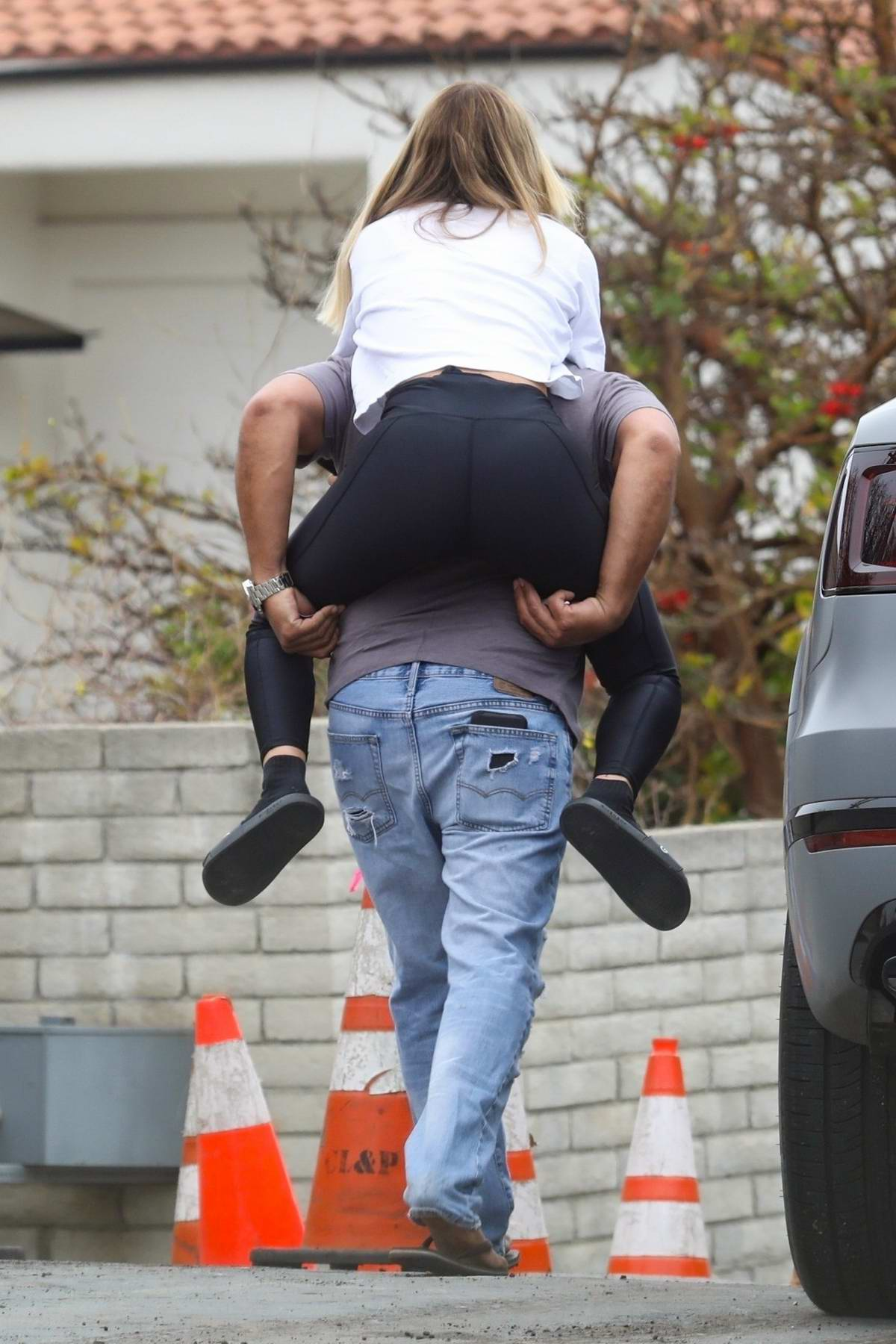 Sofia Richie wears a white tee and black leggings while out piggybacking on a friend in Malibu, California