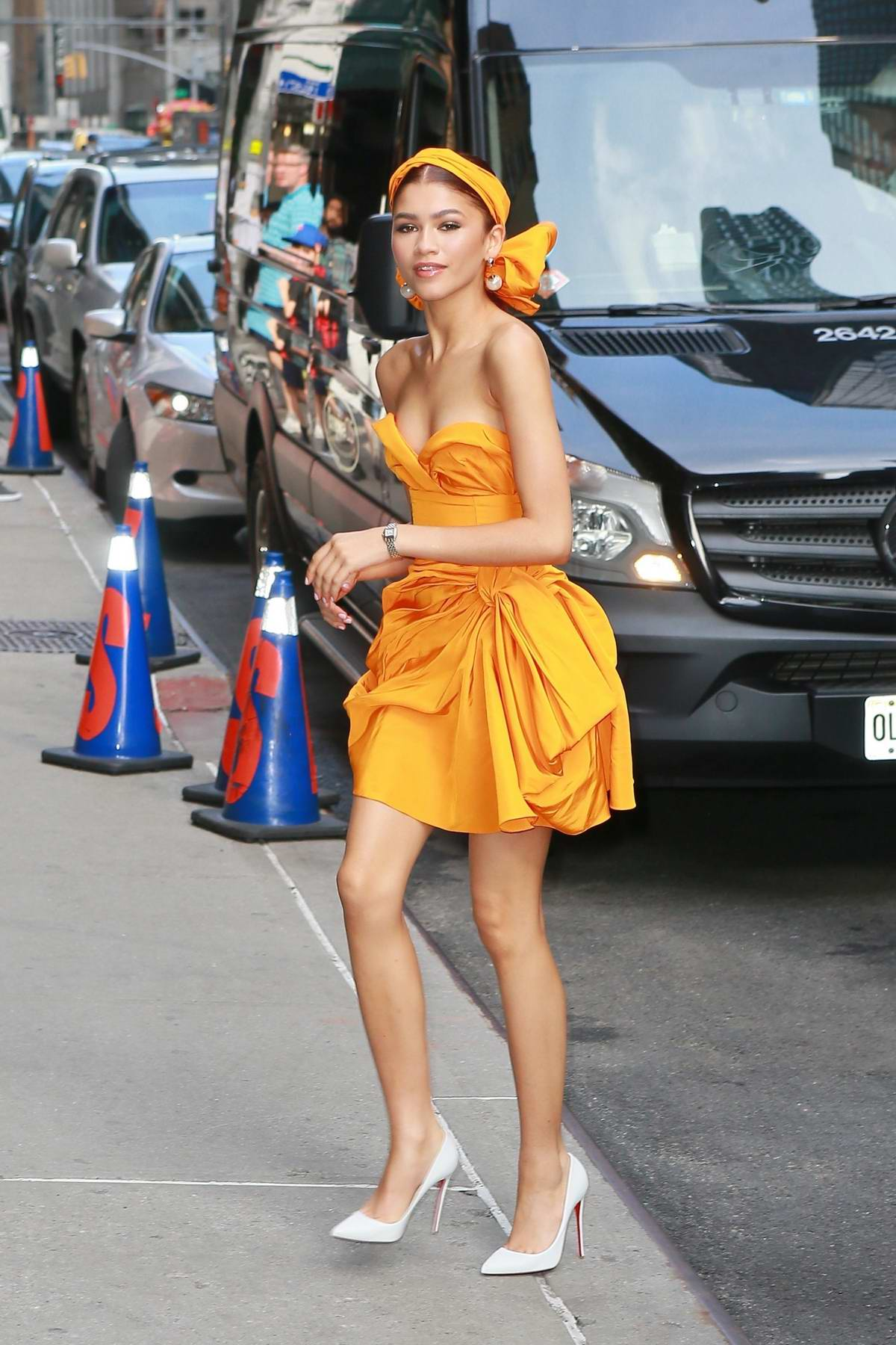 Zendaya looks vibrant in orange as she arrives for her appearance at 'The Late Show With Stephen Colbert' in New York City