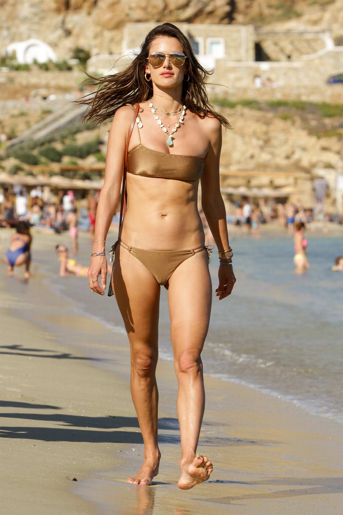 Alessandra Ambrosio stuns in metallic gold bikini while taking a stroll at the beach with friends in Mykonos, Greece