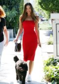 Alexis Ren looks stunning in a red dress while out with her dog in West Hollywood, Los Angeles