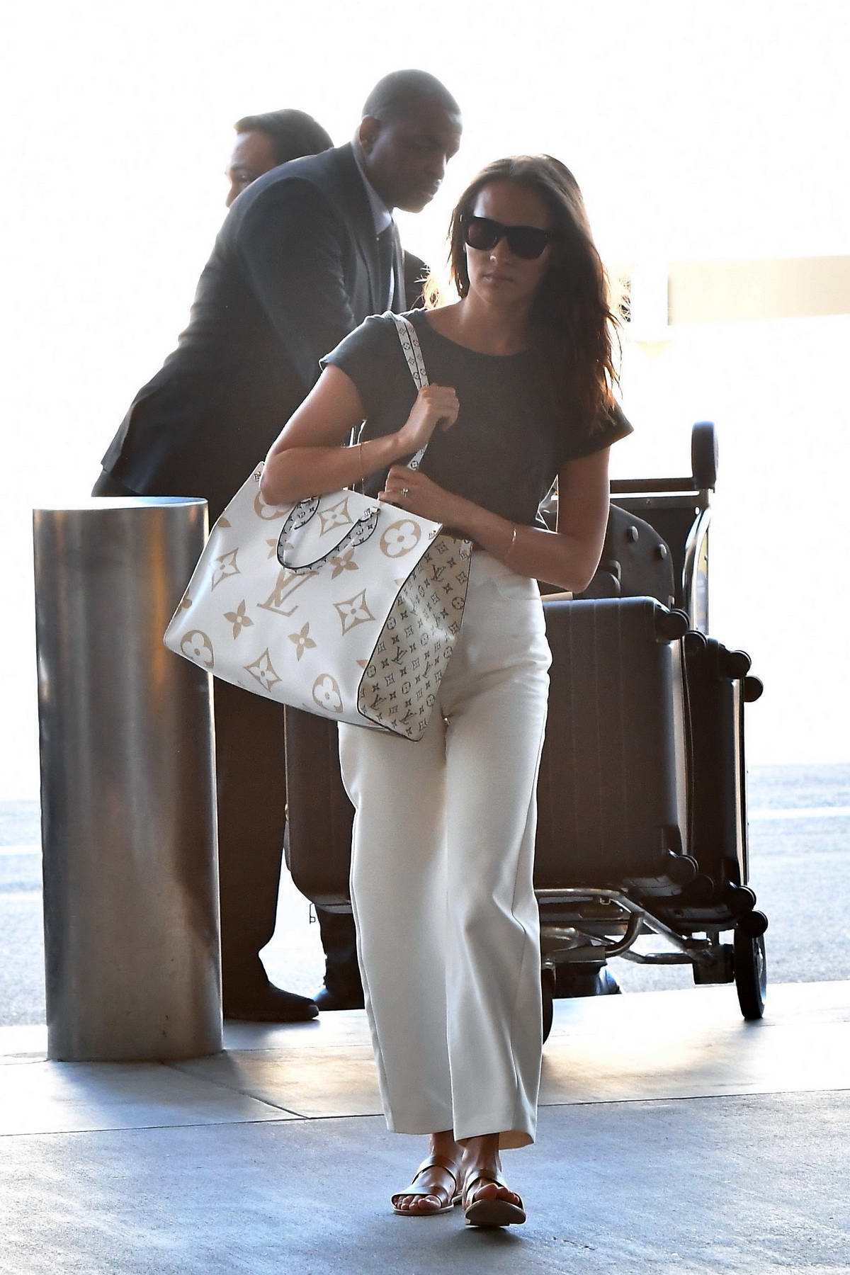 Alicia Vikander carries a large Louis Vuitton bag as she arrives at LAX Airport in Los Angeles