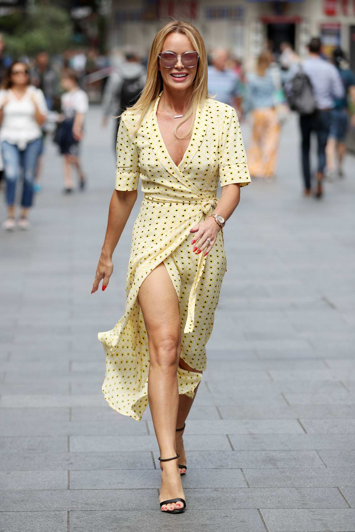 Amanda Holden flashes long legs in a yellow polka dot wrap dress while leaving Heart Radio, Global House in London, UK