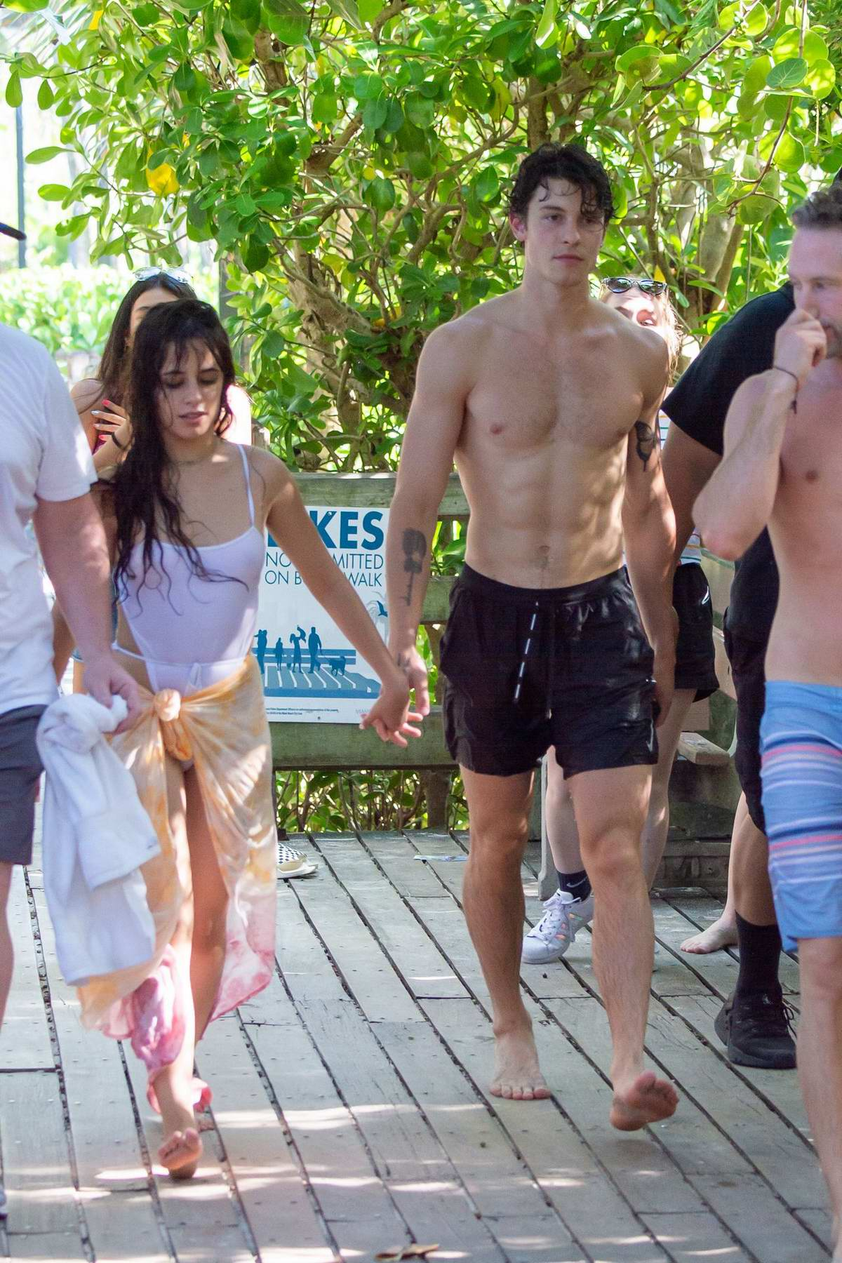 camila cabello wears a white swimsuit during a pda-filled beach day