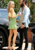 Charlotte McKinney greets a friend as she leaves a party on 4th of July weekend in Malibu, California