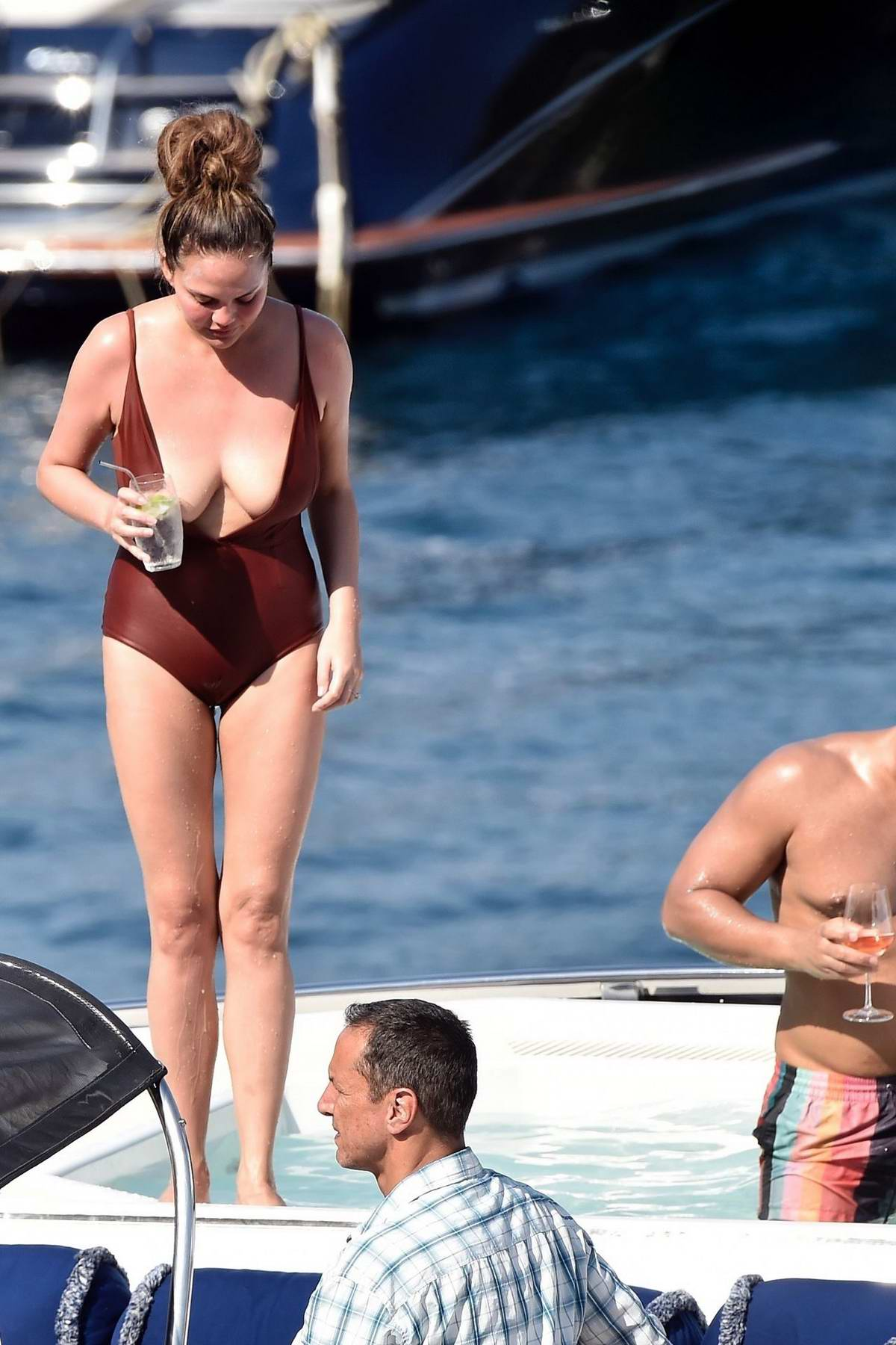 Chrissy Teigen relaxes on a yacht in a brown swimsuit while on vacation in Portofino, Italy