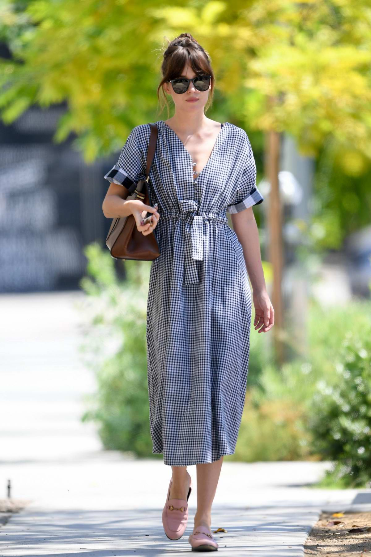 Dakota Johnson looks lovely in a gingham summer dress and pink Gucci loafers while out for a stroll in Los Angeles