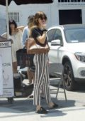 Dakota Johnson looks stylish in stripes while waiting for her ride after visiting a Beauty Spa in San Fernando Valley, California