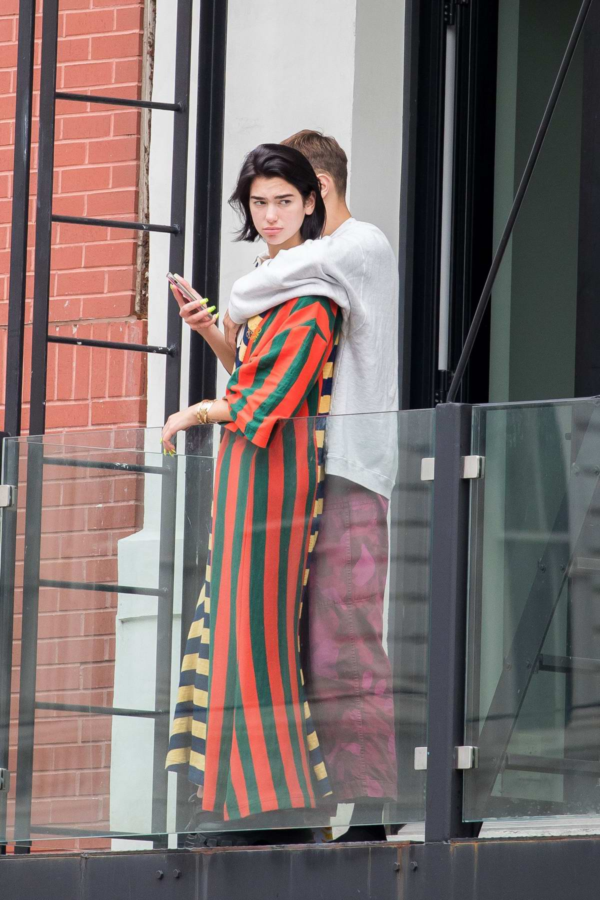 Dua Lipa and Anwar Hadid hang out on the balcony of an apartment complex in New York City