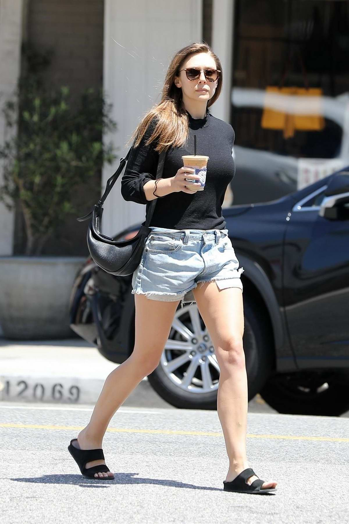 Elizabeth Olsen rocks a black top and denim shorts while out for an iced coffee at Alfred's in West Hollywood, Los Angeles