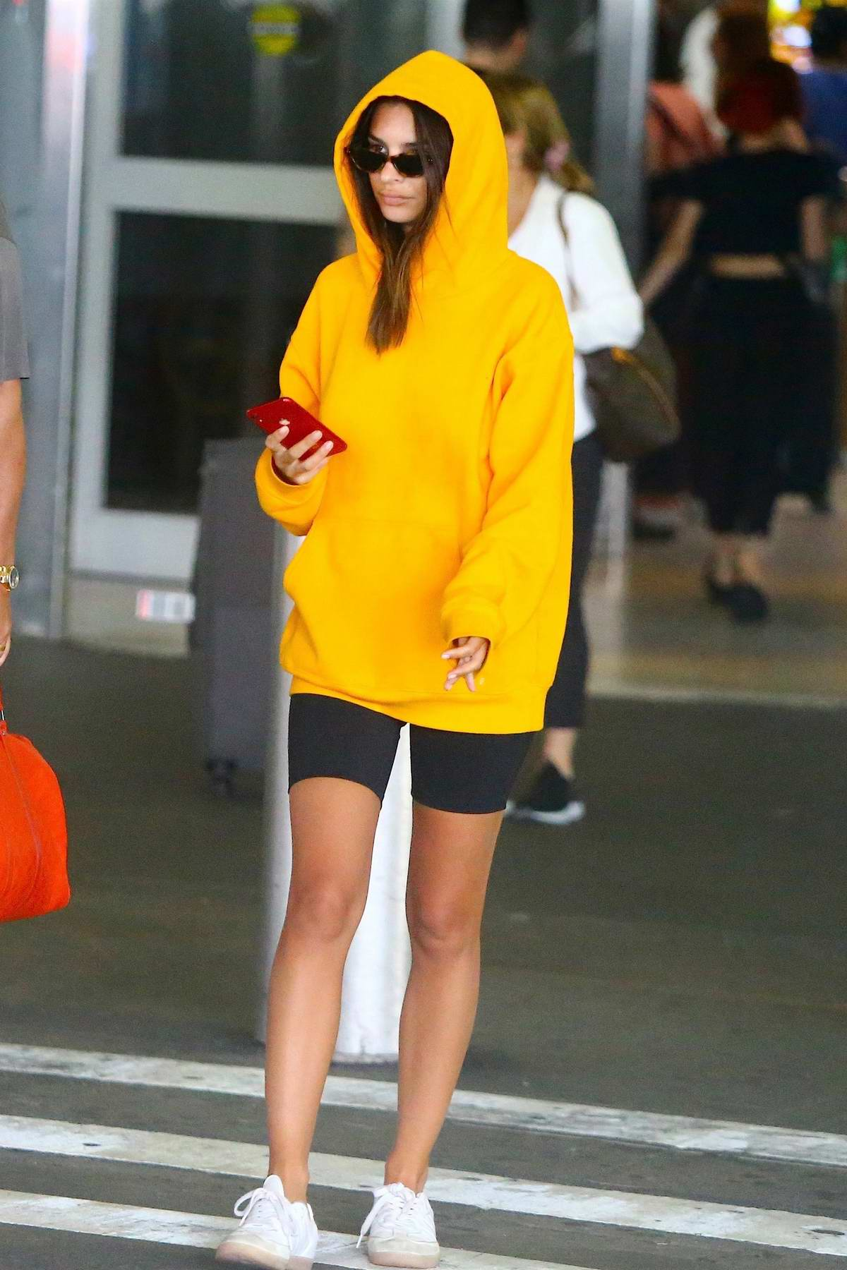 Emily Ratajkowski rocks yellow hoodie and black legging shorts as she touches down at JFK Airport in New York