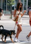 Emily Ratajkowski wears a floral print minidress and white sneakers while out for stroll with her dog in New York City