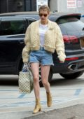 Emma Roberts wears a knitted yellow cardigan and denim shorts during a shopping trip to Louis Vuitton in Los Angeles