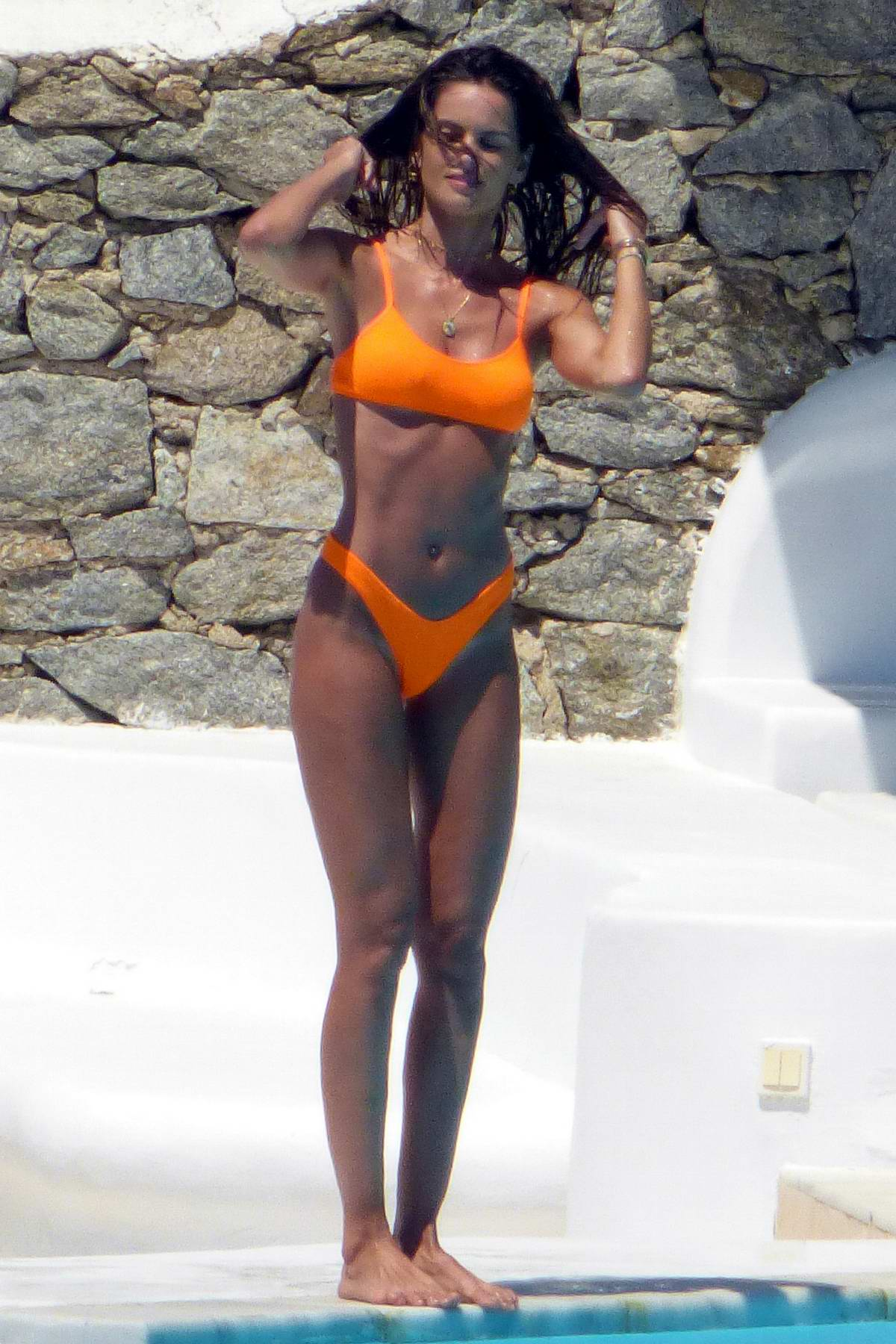 Izabel Goulart stuns in an orange bikini while having fun at the pool on Mykonos Island, Greece