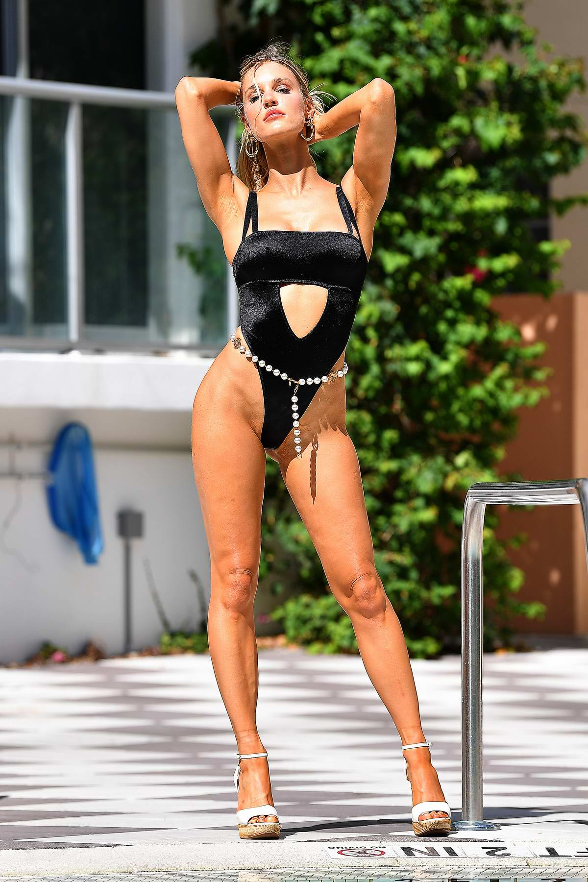 Joy Corrigan sizzles in a black swimsuit while posing for photos by the pool in Miami Beach, Florida