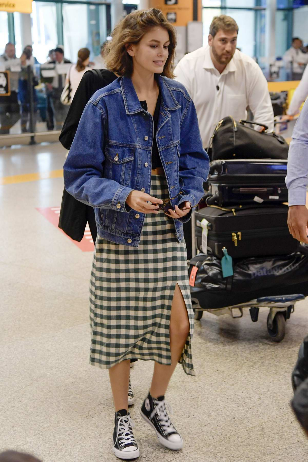 Kaia Gerber looks trendy in a plaid skirt, black top and denim jacket as touches down at Fiumicino Airport in Rome, Italy